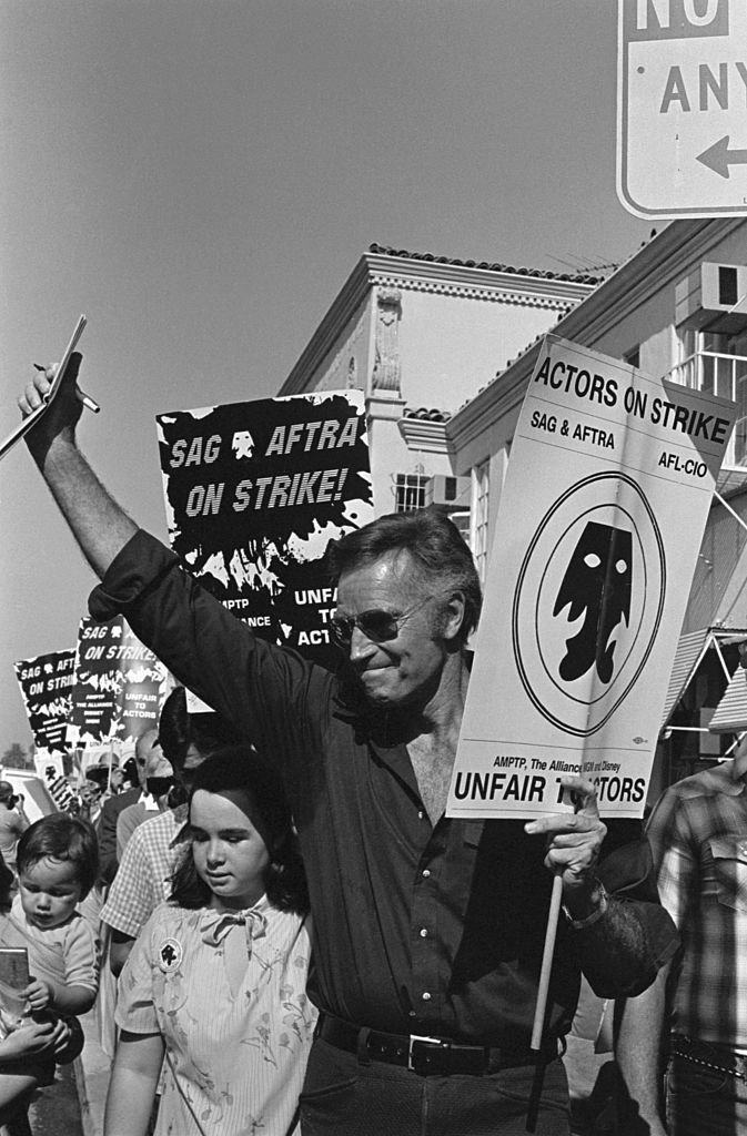 Charlton Heston waves as he carries his picket sign as members of the striking Screen Actors Guild picket Paramount Picture's studio | Photo: Getty Images