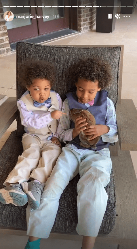 Two of Marjorie and Steve Harvey's grandchildren playing with a rabbit while sitting on a chair. | Source: Instagram/marjorie_harvey