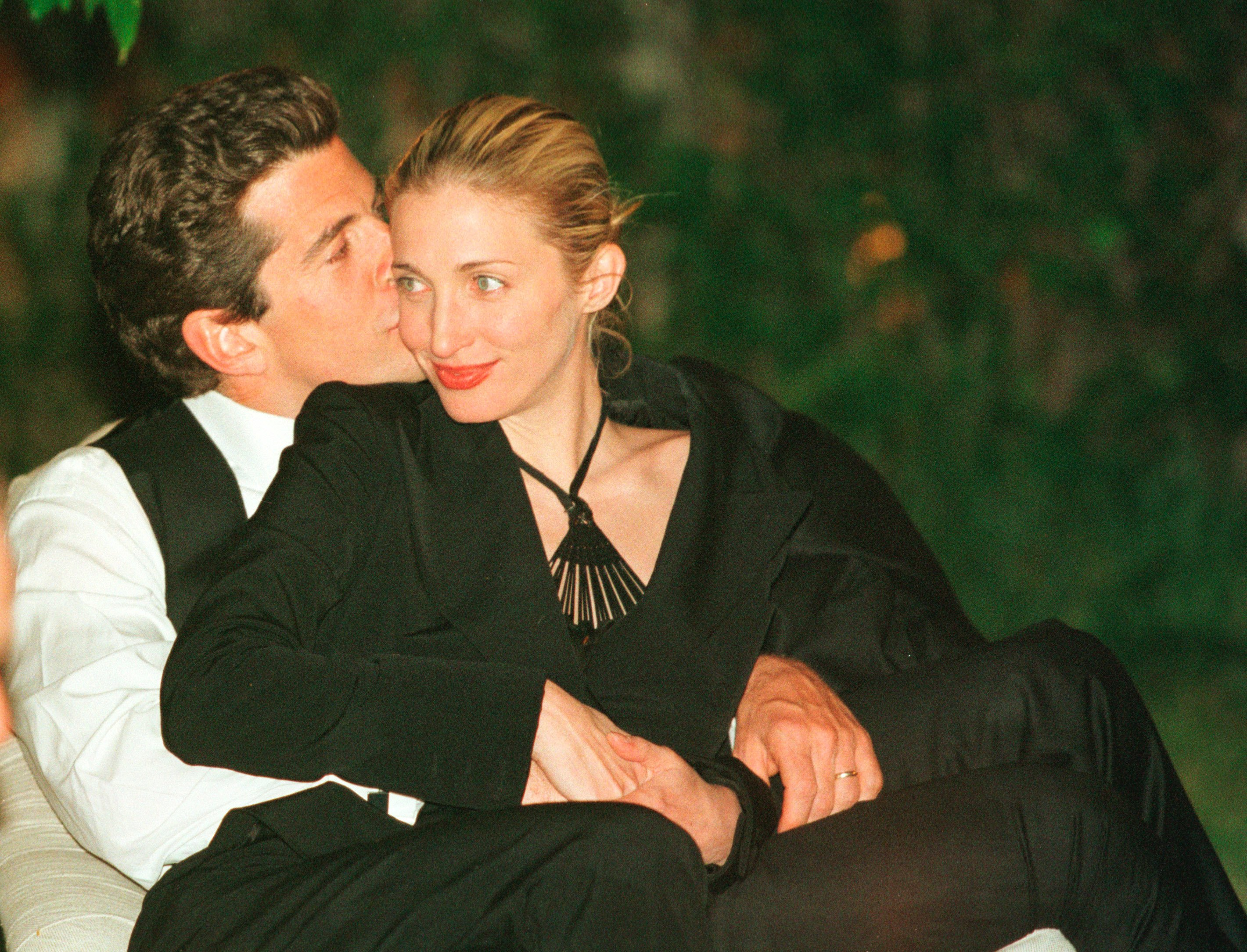 John F. Kennedy, Jr. gives his wife Carolyn a kiss on the cheek during the annual White House Correspondents dinner May 1, 1999 in Washington, D.C. | Photo: Getty Images