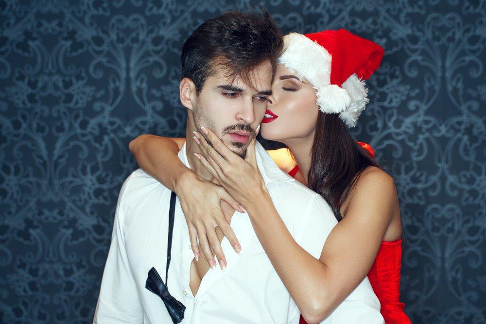 Une femme déguisée en mère noël sexy qui chuchote et déshabille un homme. | Source : Shutterstock