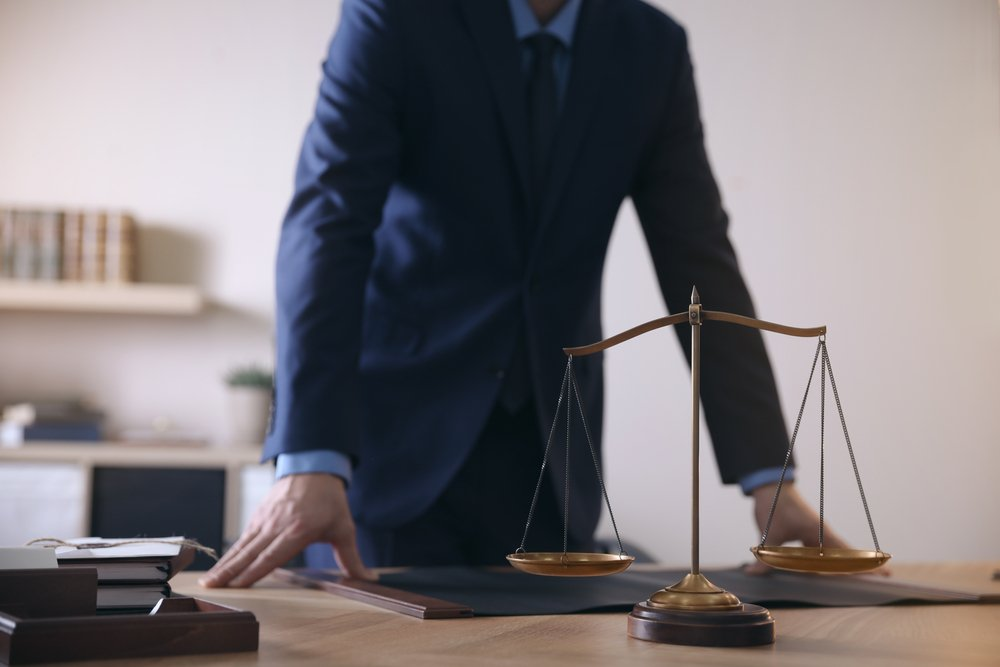 A photo of a male lawyer by table in office standing behind the scales of justice. | Photo: Shutterstock