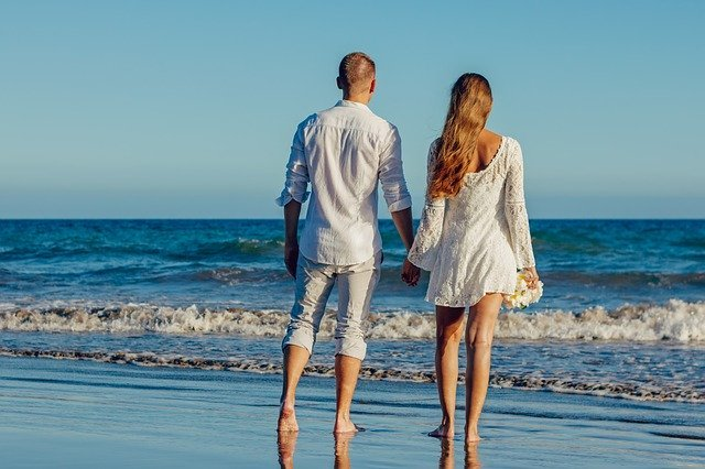 Young couple looking carefree on the beach | Photo: Pixabay
