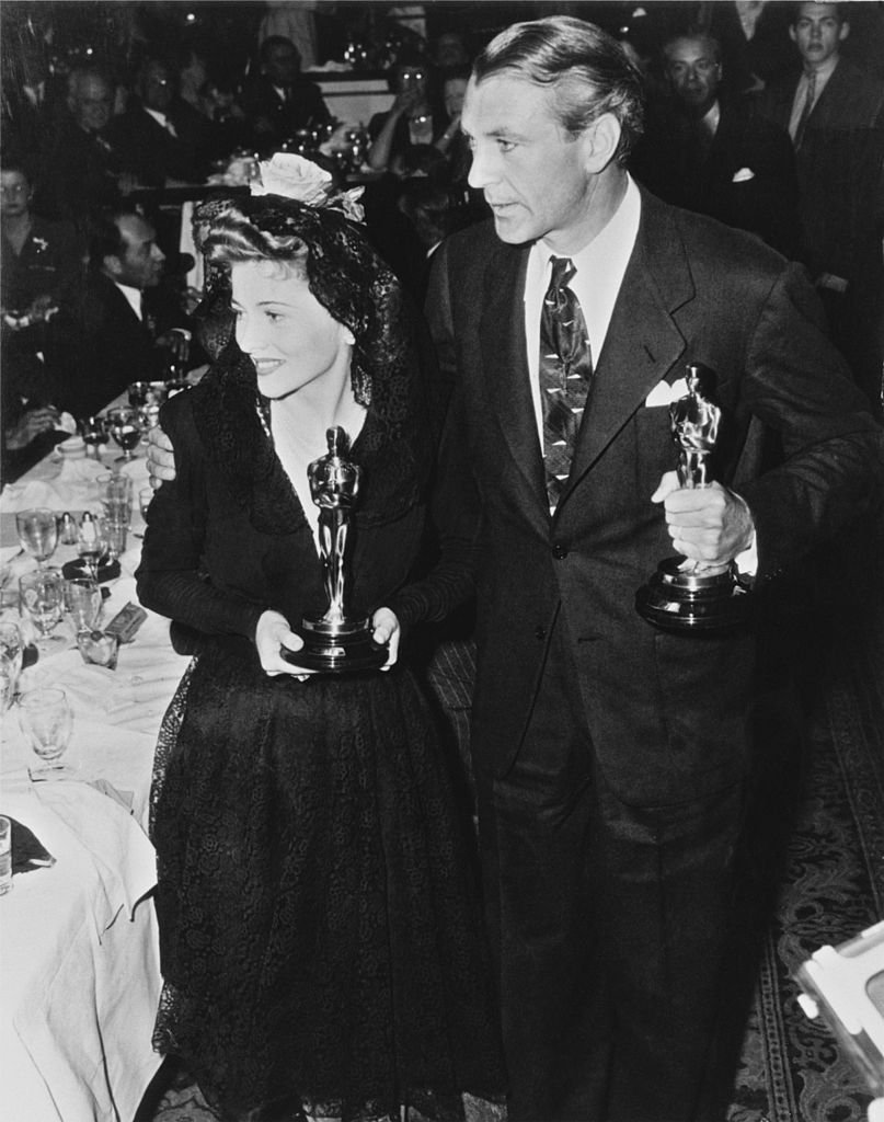 Joan Fontaine (1917 - 2013) holding her 'Best Actress' Oscar for her role in 'Suspicion', and American film actor, Gary Cooper, with his 'Best Actor' Oscar for his role in 'Sergeant York' at the 14th Academy Awards at the Biltmore Bowl, Los Angeles Biltmore Hotel, USA, 26th February 1942. | Source: Getty Images