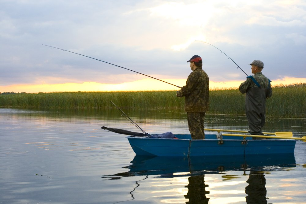 Two men on a boat fishing. | Photo: Shutterstock