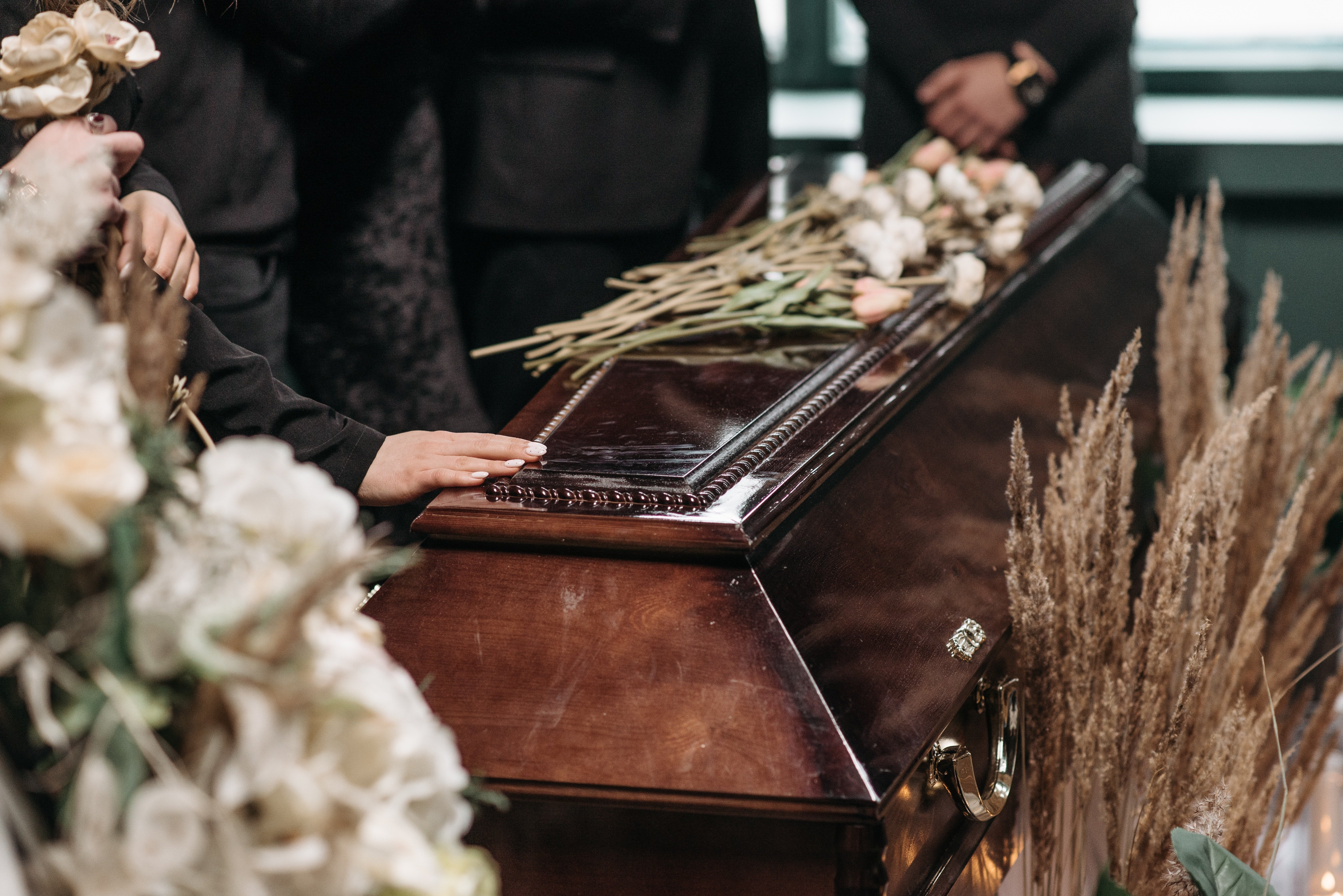 People saying goodbye to a deceased loved one   Photo: Pexels