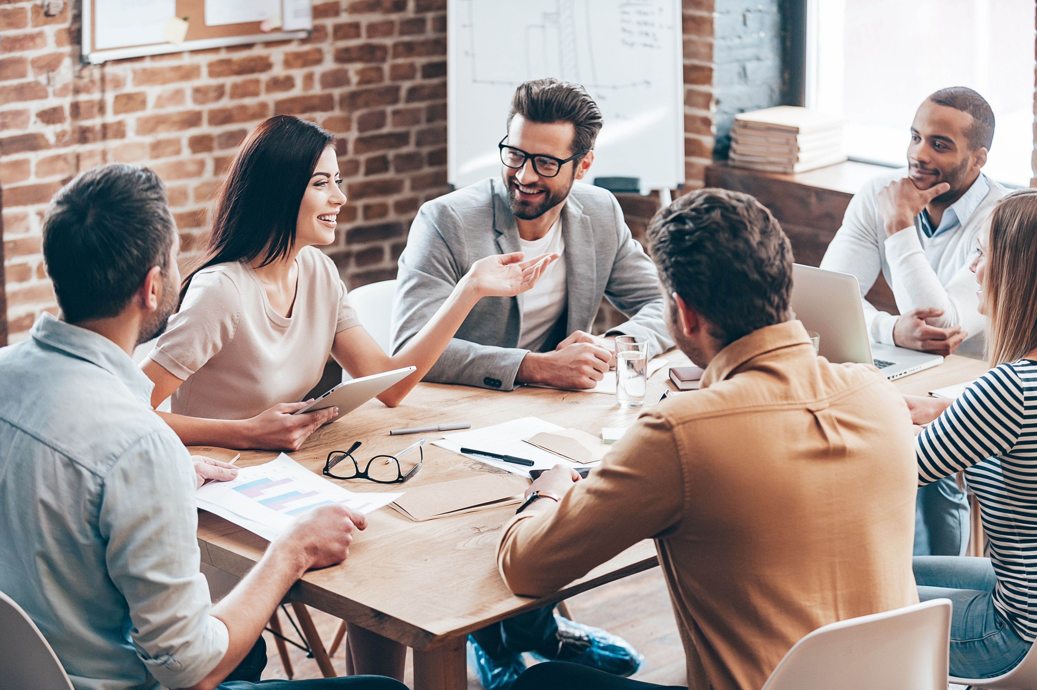 Co-workers talking on a table. | Source: Shutterstock