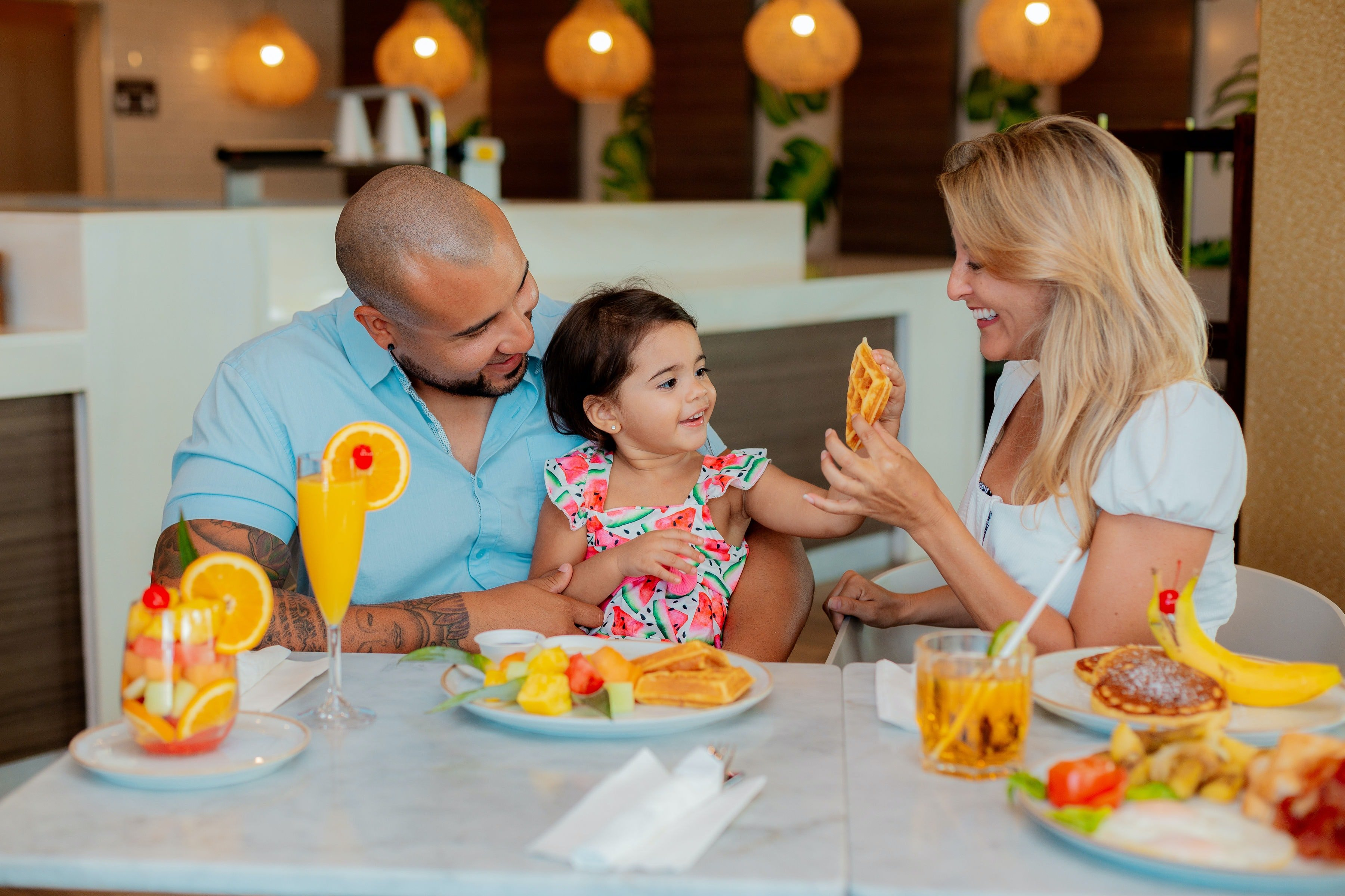 Couple dining in a restaurant with their kid | Photo: Unsplash