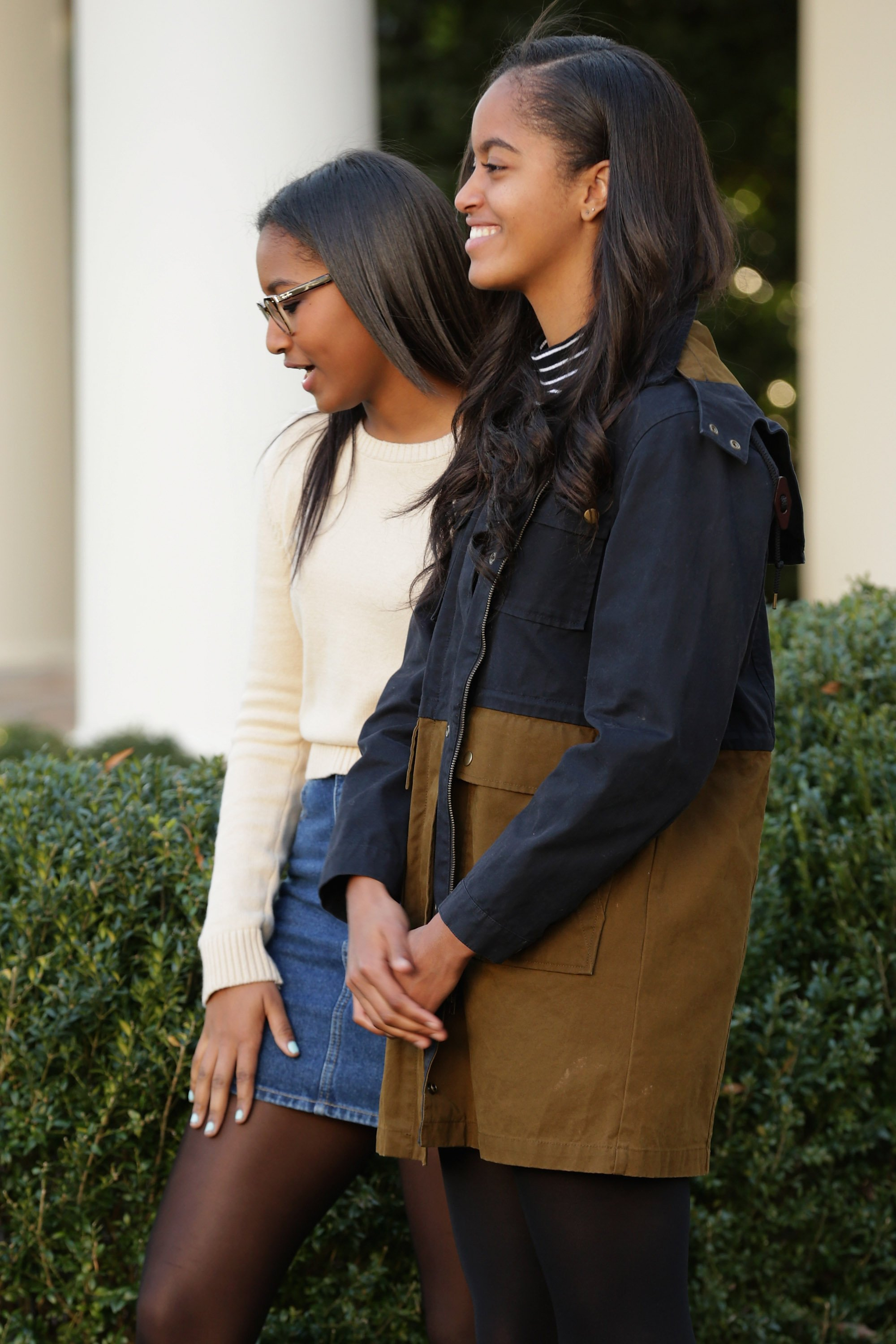 U.S. President Barack Obama's daughters Sasha (L) and Malia participate in the annual turkey pardoning ceremony in the Rose Garden at the White House November 25, 2015, in Washington, DC. | Source: Getty Images.