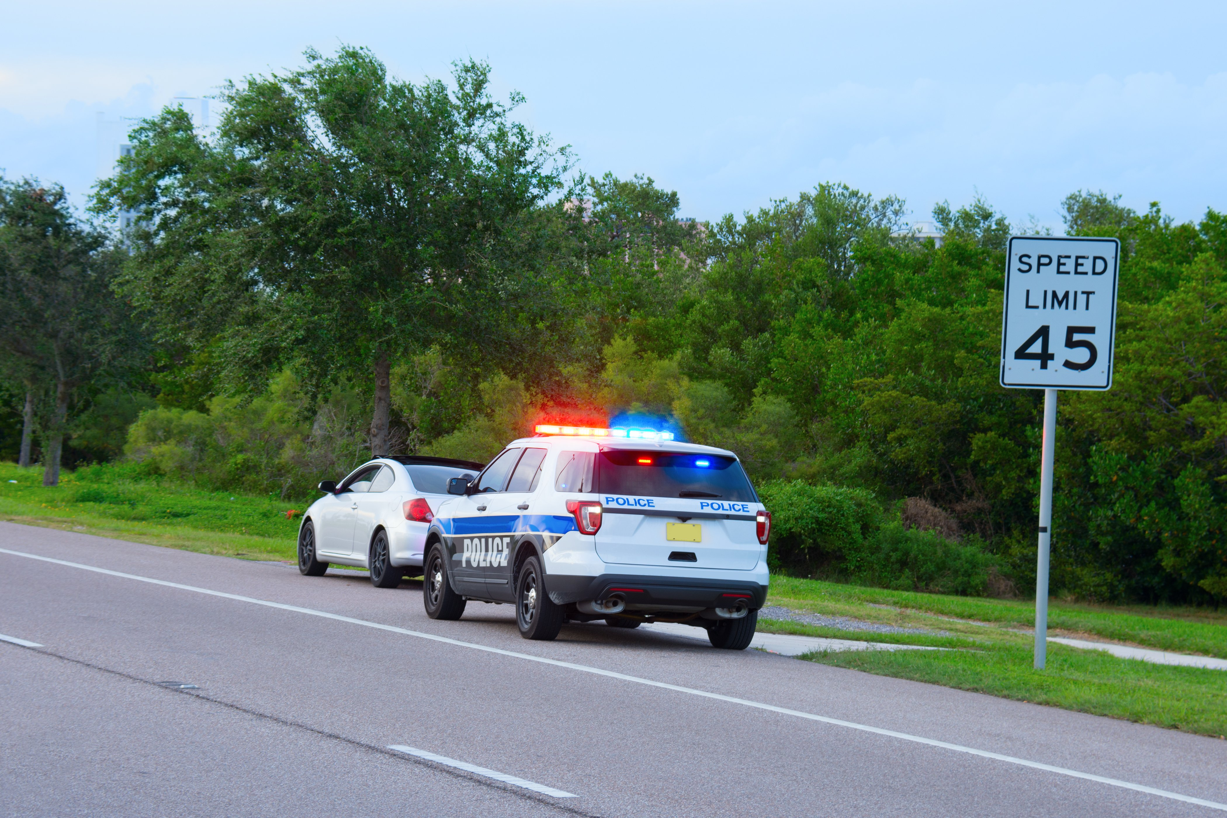 A police vehicle appears to be pulling a car over.   Photo; Shutterstock