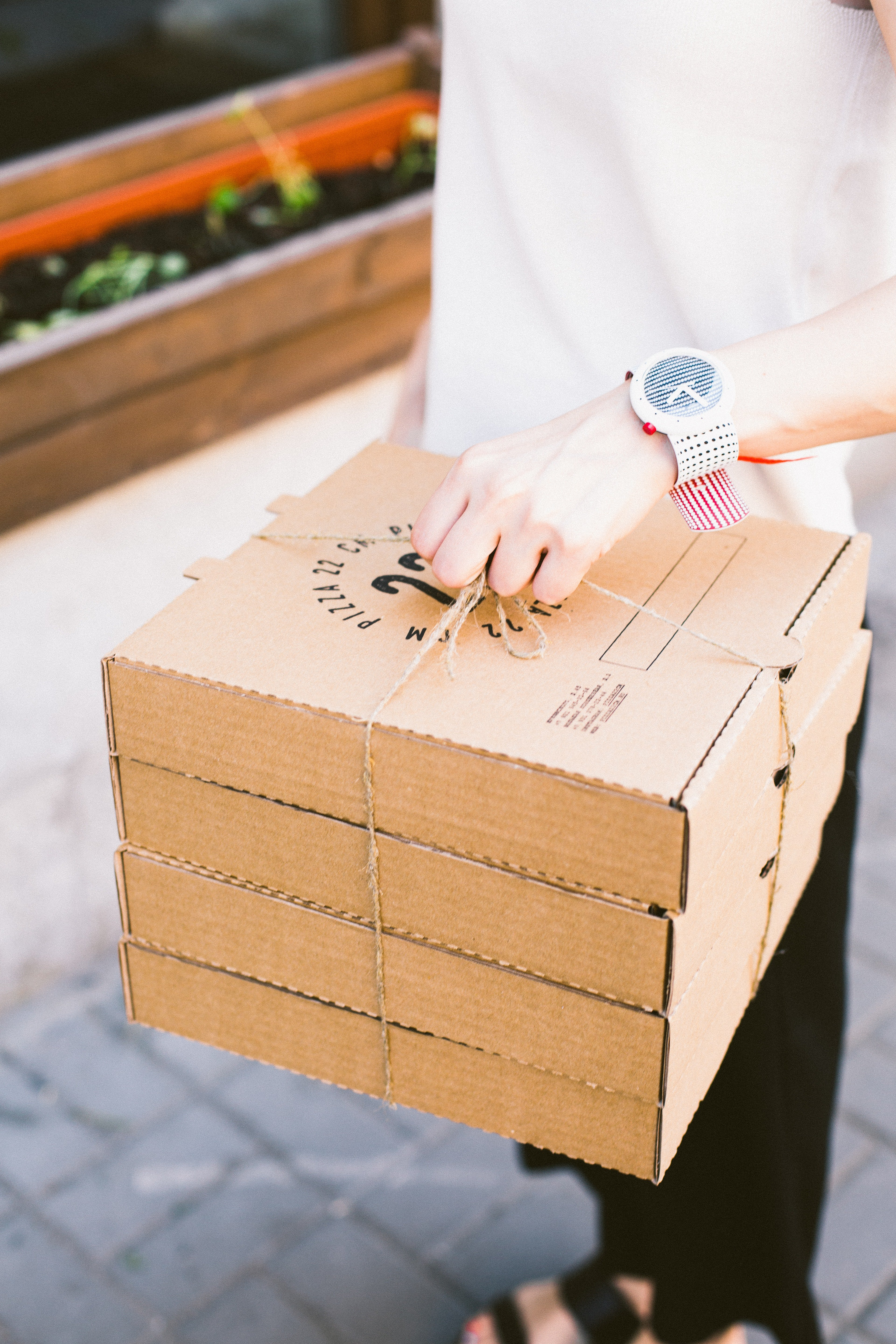 Person in a white shirt holding a stack of pizza boxes | Photo: Pexels