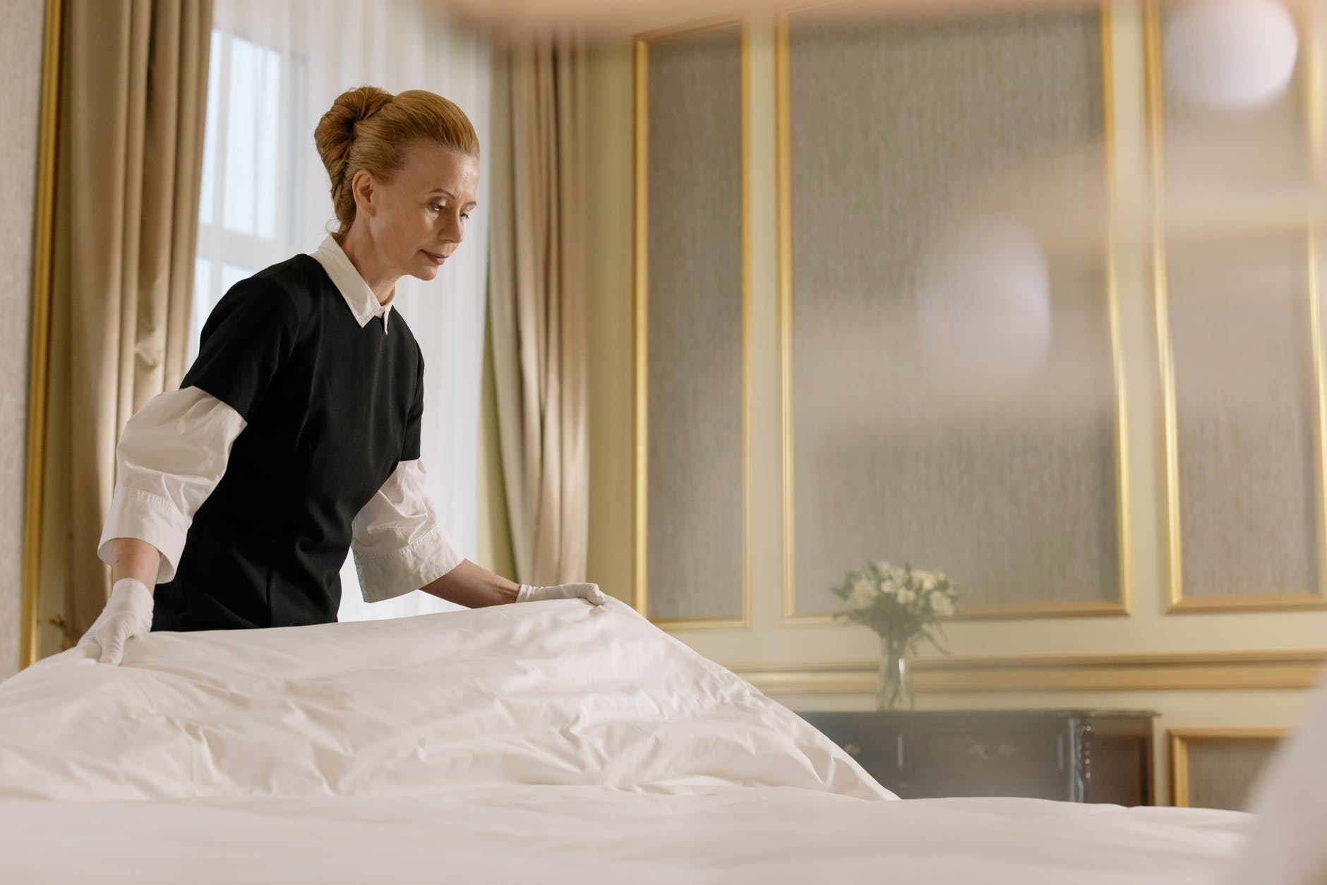 A housemaid arranging a bed cover | Source: Pexels