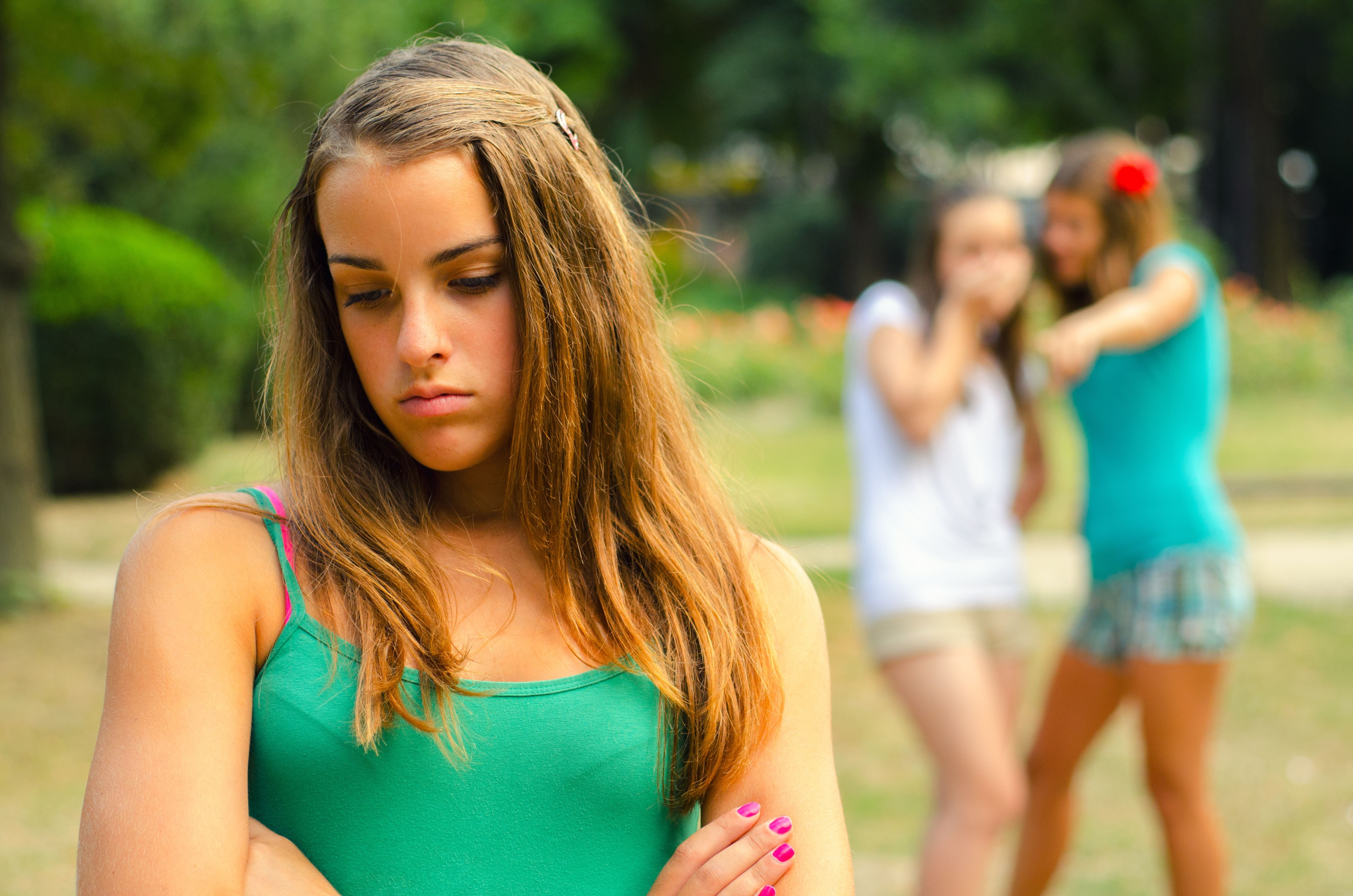 A teen looks sad while her peers tease her.   Source: Shutterstock