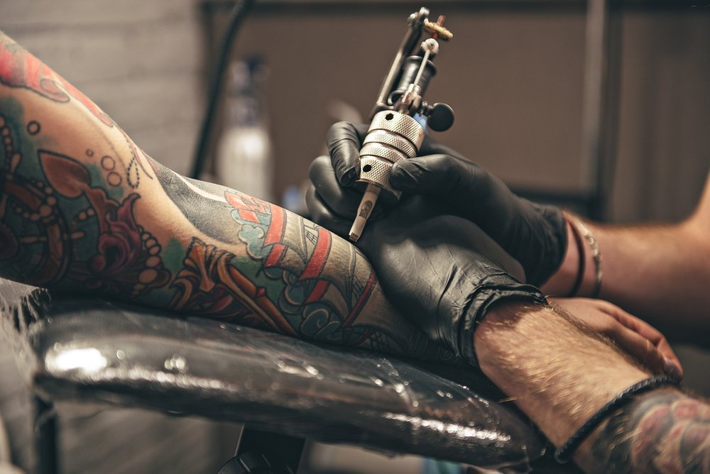 A man getting a tattoo from an artist. | Photo: Shutterstock