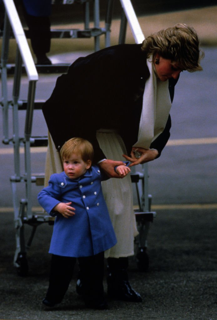Diana, Princess of Wales clutches baby Prince Harry by the hand when they arrive at Aberdeen Airport on their way to Balmoral | Photo: Getty Images