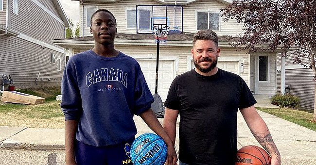 Two men posing for a photo while holding a  basketball | Photo: facebook.com/GlobalNews