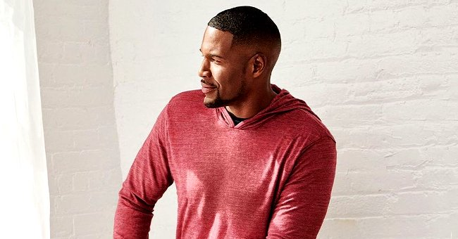 Michael Strahan Models His Own Clothing Line as He Poses in a Red Hoodie & Denim Pants