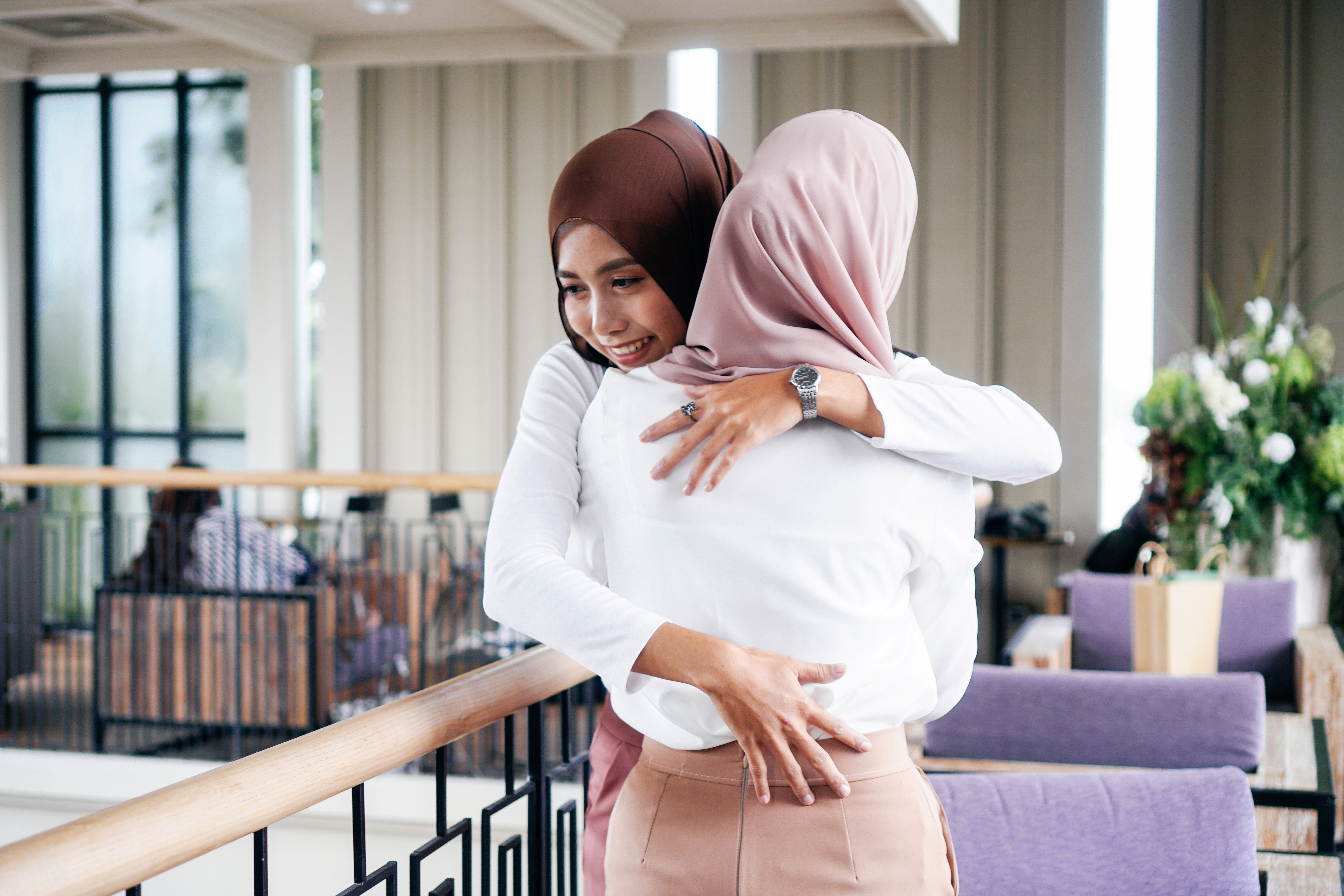 Portrait of young Asian muslim women in happy smile with hijab or head scarf hugging each other indoors|Photo: Getty Images