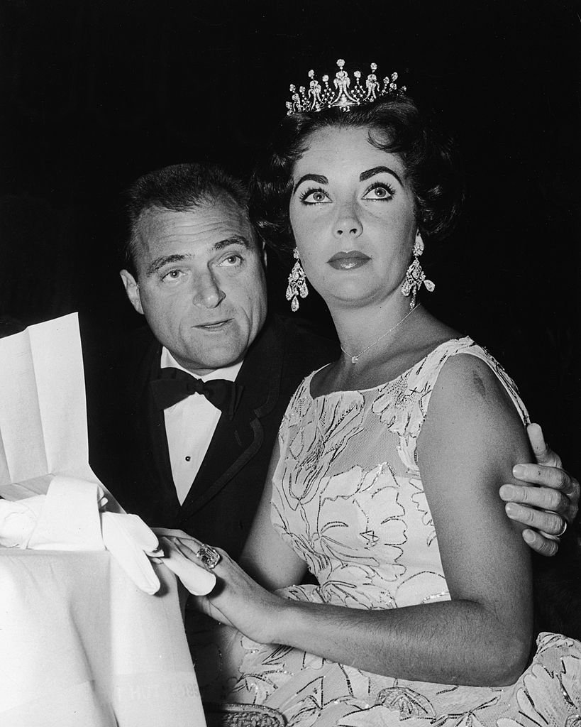Elizabeth Taylor sits with her third husband, American film producer Mike Todd, at a Golden Globe Awards ceremony at the Coconut Grove nightclub, Hollywood, California, 1957 | Photo: Getty Images