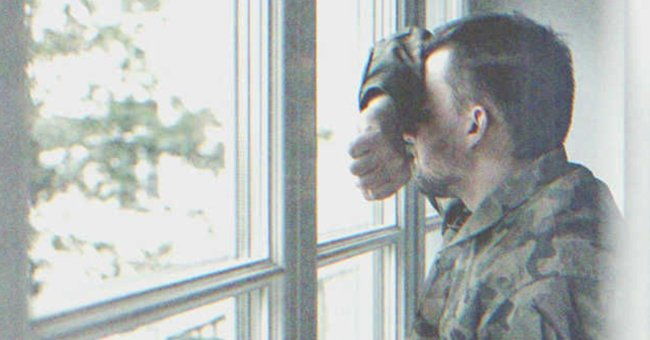 A man from the army looks out a window. | Source: Shutterstock