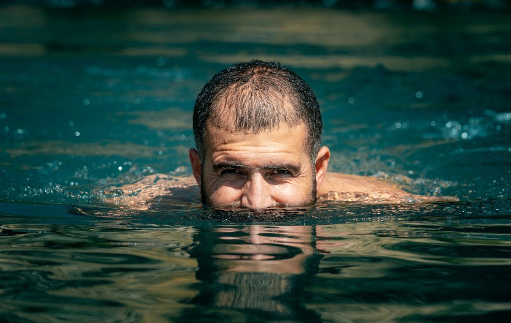A photo of a man swimming with his face above water. | Photo: Shutterstock