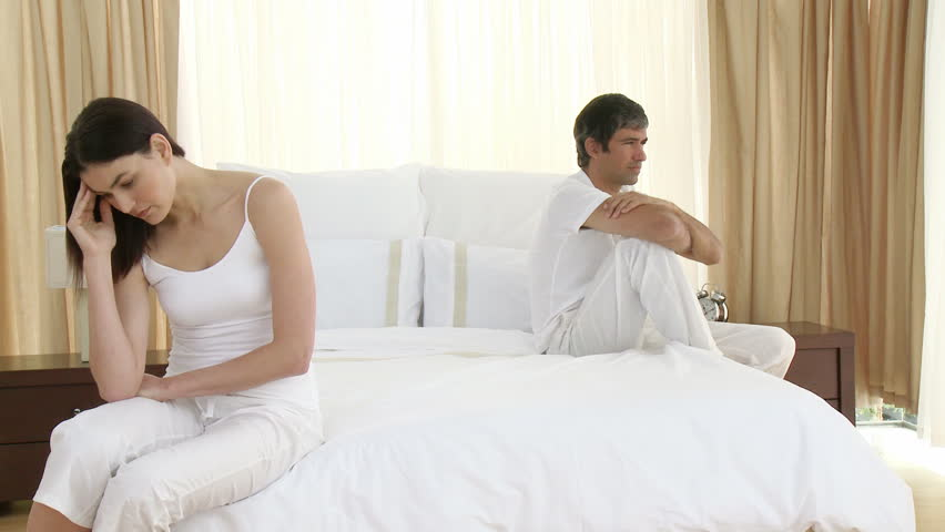 Couple looking distressed on the bed, after an argument | Photo: Shutterstock
