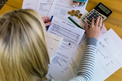 A woman looking through unpaid bills. | Source: Shutterstock.