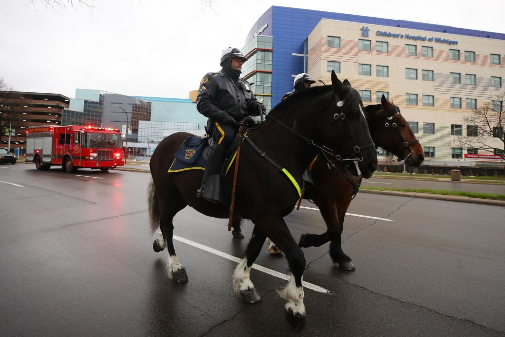 Members of the Detroit Mounted Police pass by the Children's Hospital of Michigan during a parade to support healthcare workers work during the COVID-19 pandemic on April 17, 2020 in Detroit, Michigan | Photo: Getty Images