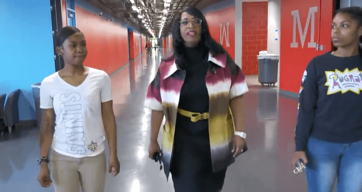 Principal Carlotta Brown walking down the hallway with two students