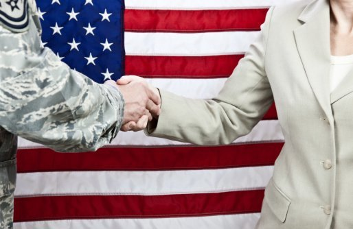 Handshake between enlisted military member and a female civilian | Photo: Getty Images