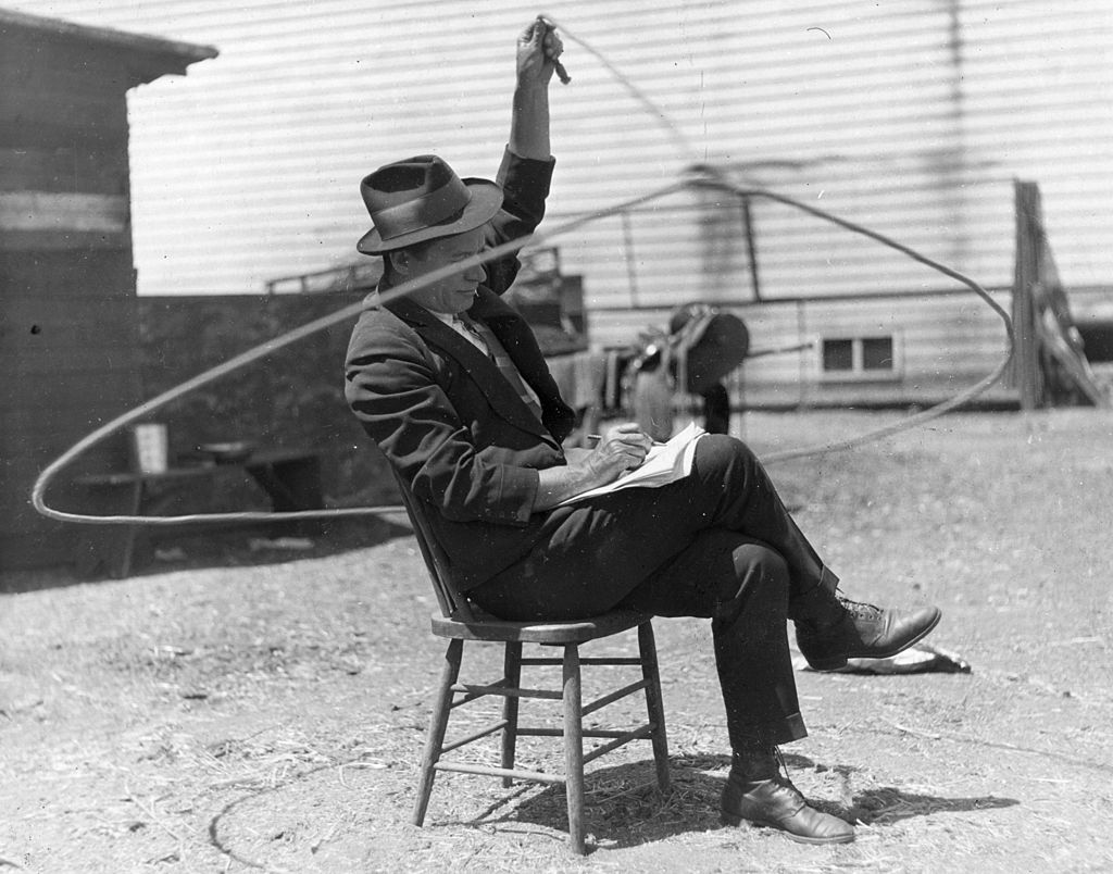 Will Rogers (1879 - 1935), American rustic comedian playing with a lasso whilst writing himself some notes | Photo: Getty Images