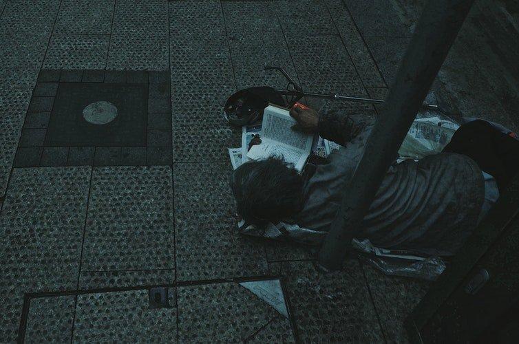 Un pauvre enfant seul,dans la rue,qui lit un livre | Photo : Unsplash