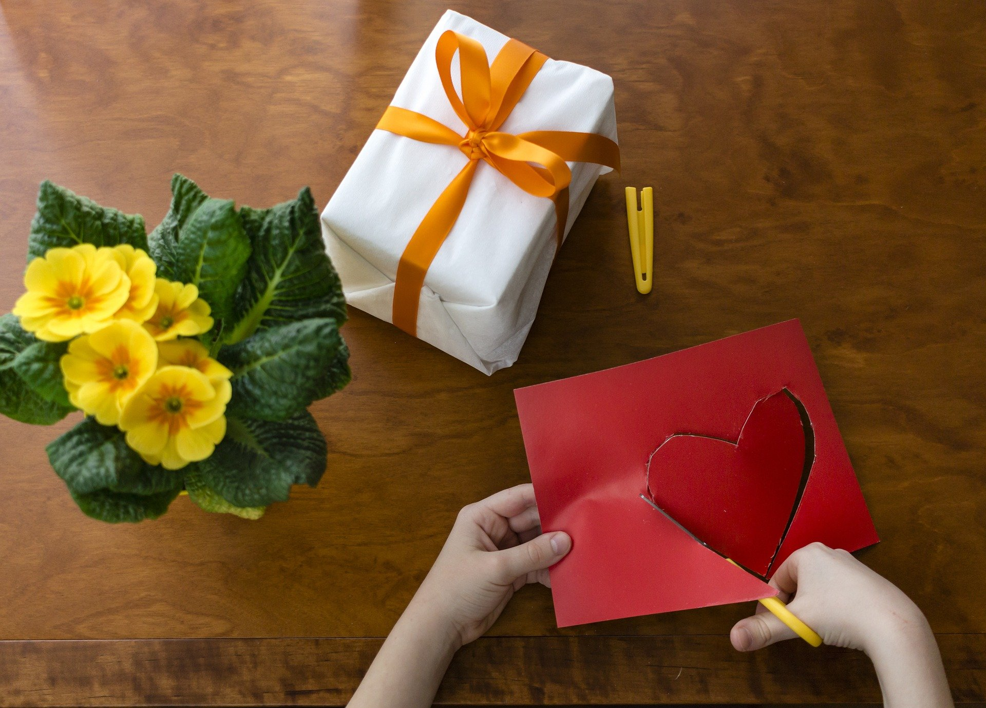 Pictured - A kid cutting out a heart shape next to wrapped gift and flowers | Source: Pixabay