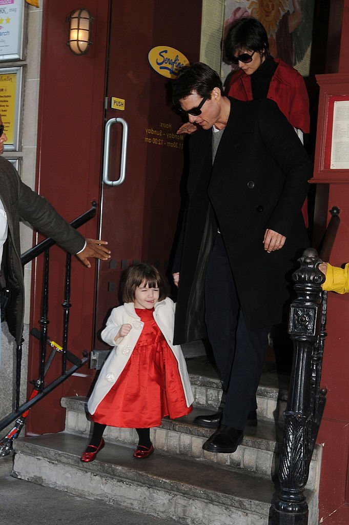 Tom Cruise (C), his wife Katie Holmes and their daughter Suri Cruise walk out of a restaurant November 28, 2008 | Getty Images