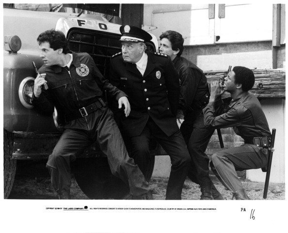 George Gaynes, Andrew Rubin and Michael Winslow pursue a criminal in a scene from the film 'Police Academy', 1984.