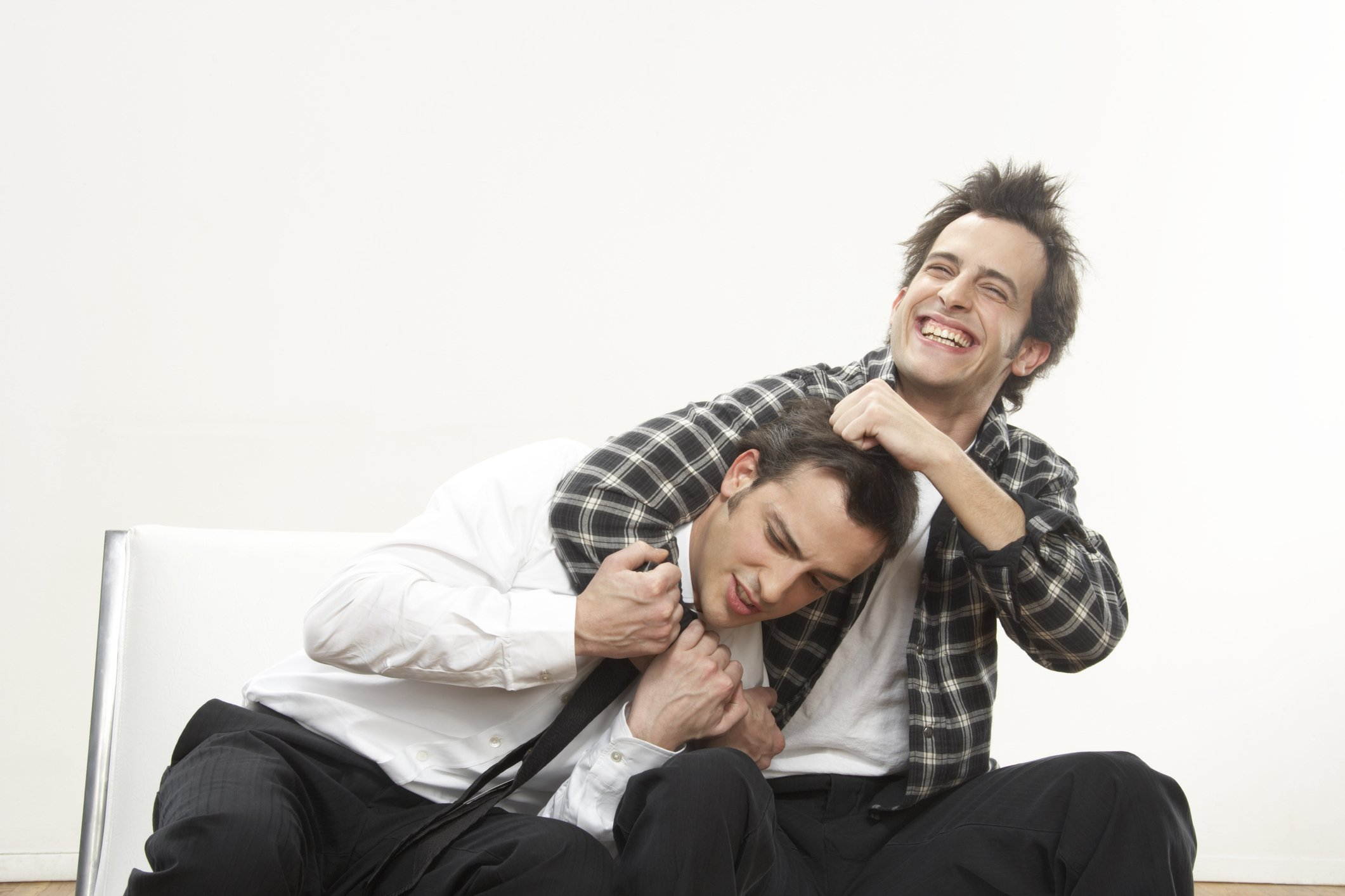 Twin brothers seated on a couch laugh out loud about something hilarious   Photo: Getty Images