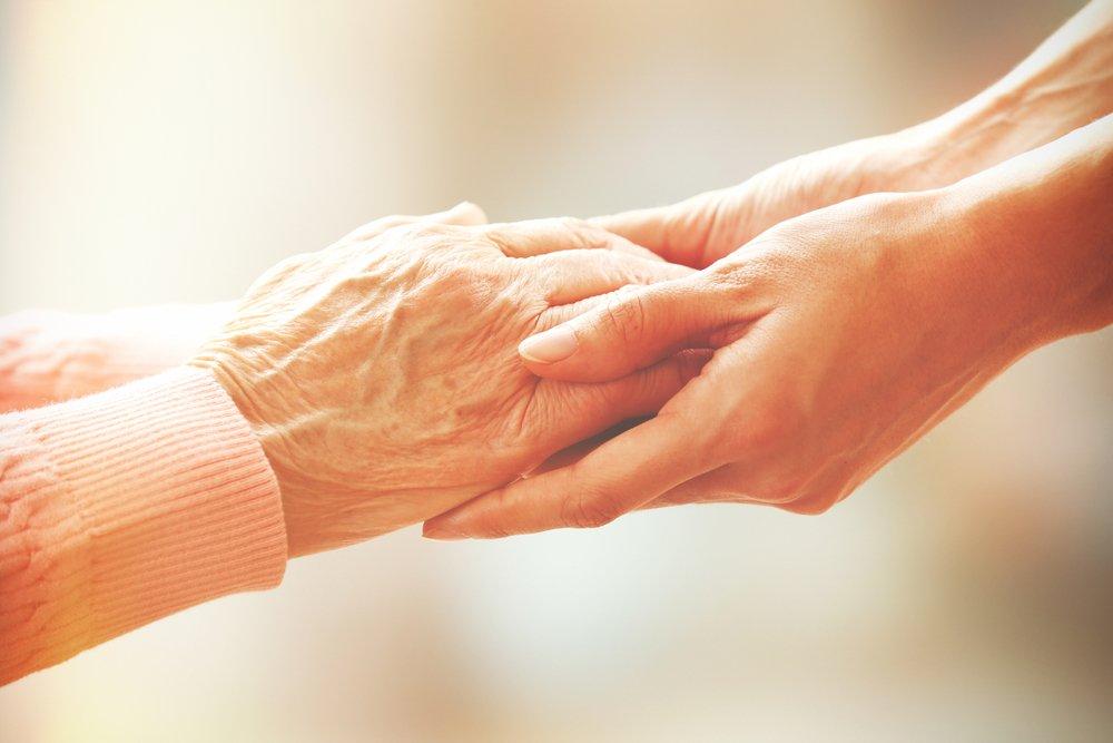 Les mains d'une personne âgée dépendante dans les mains d'une personne plus jeune.   Shutterstock