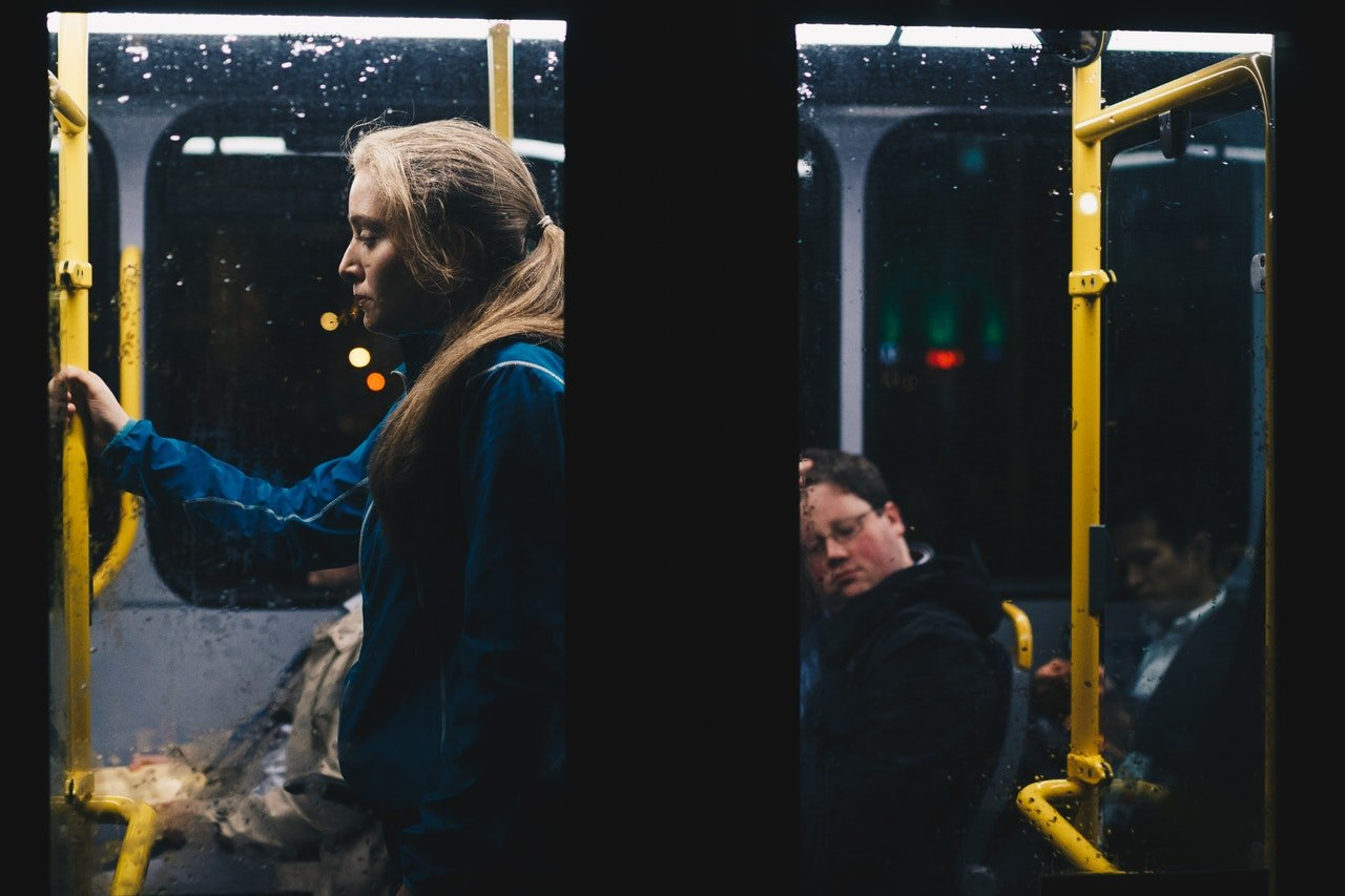 Photo of a woman standing in a bus   Photo: Pexels