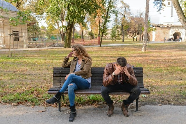 Woman and man sitting on a wooden bench | Source: Pexels