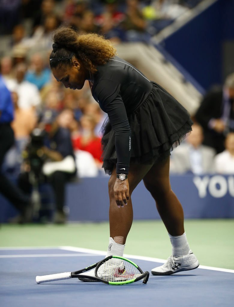 Serena Williams bends down to pick up her broken racket after throwing it to the ground in frustration during her 2018 US Open Finals match against Naomi Osaka in September 8, 2018. | Photo: Getty Images