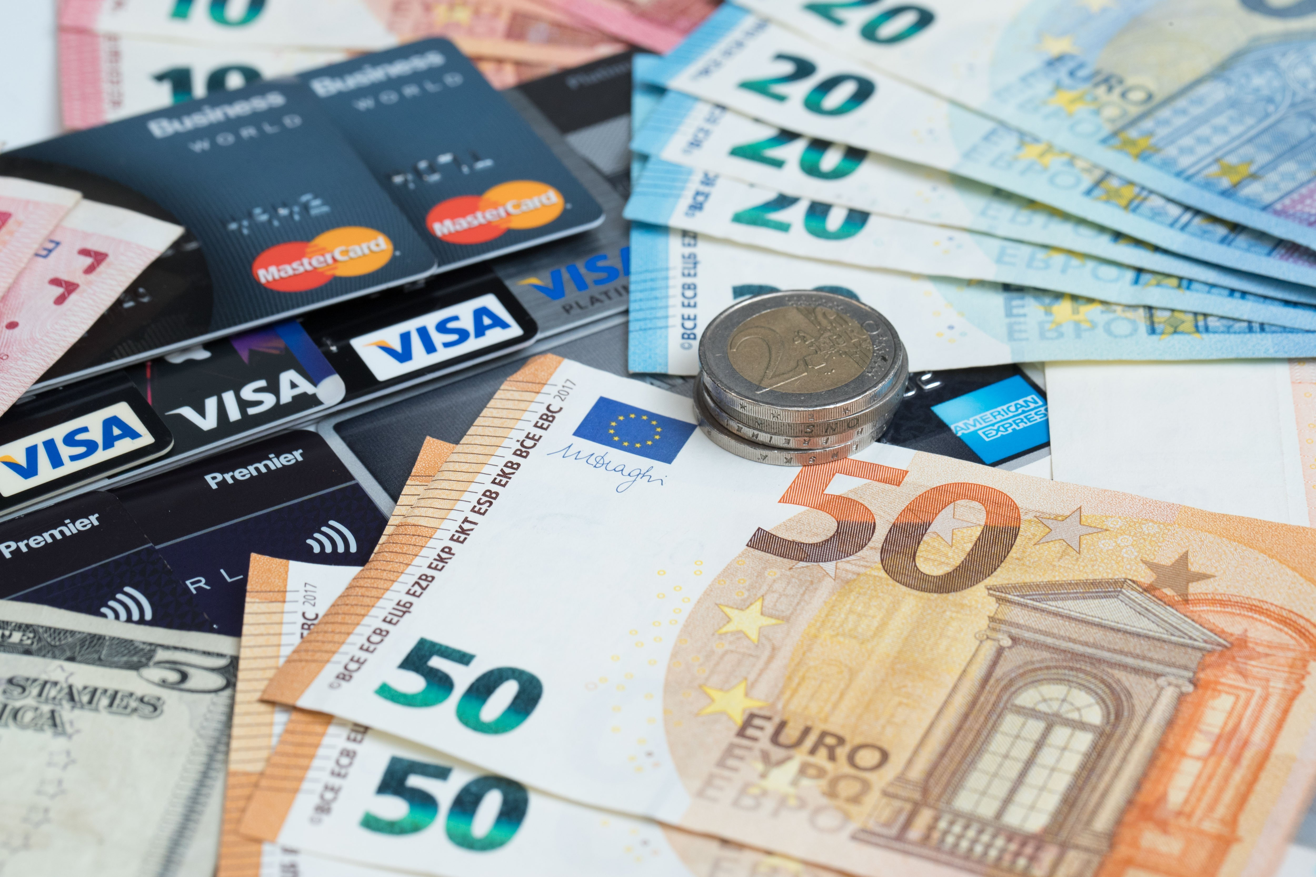 Euro coins and bills and several VISA credit cards | Photo: Getty Images