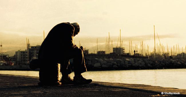 Un très vieil homme pleure tout seul sur le trottoir