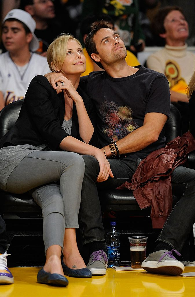Charlize Theron and Stuart Townsend watch the season opening game  | Getty Images