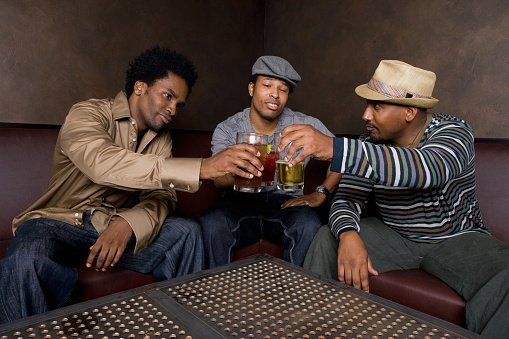 Photo of African friends toasting with beer in nightclub | Photo: Getty Images