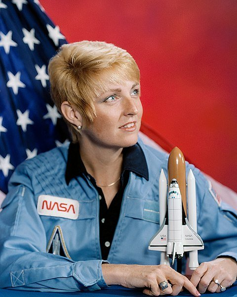 Millie Hughes-Fulford wearing NASA uniform with U.S. flag in background | Source: Wikimedia Commons