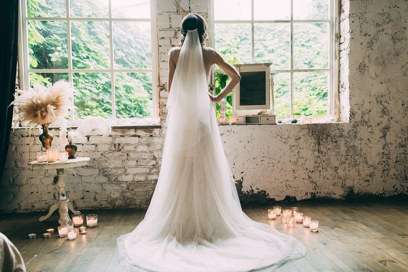 A woman wearing a wedding dress with a long veil hanging from her head | Image: Shutterstock.
