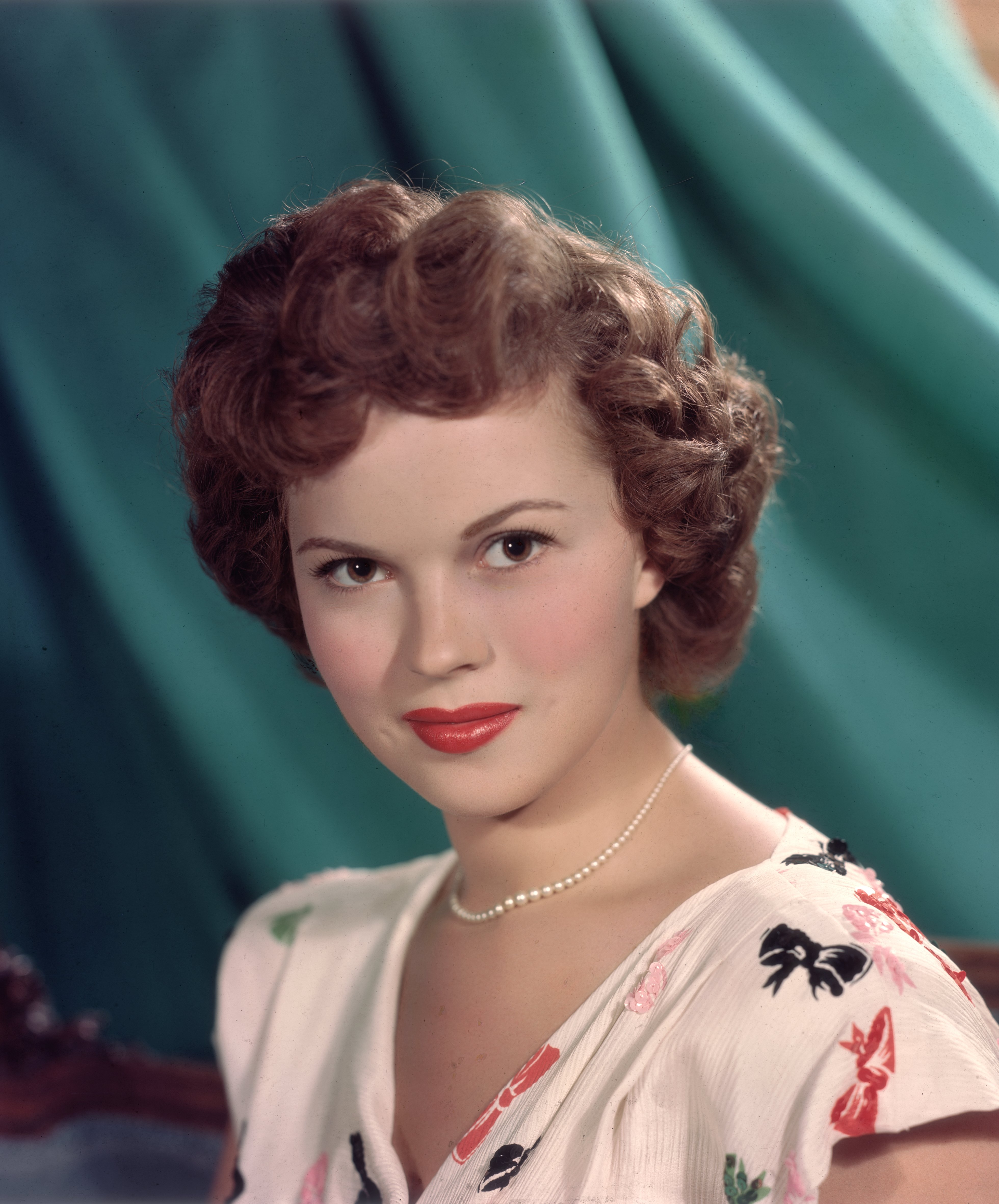 Headshot studio portrait of American actor Shirley Temple, in front of a green backdrop, wearing a short sleeve white blouse with a colored bows pattern and a pearl necklace. circa 1955 | Source: Getty Images