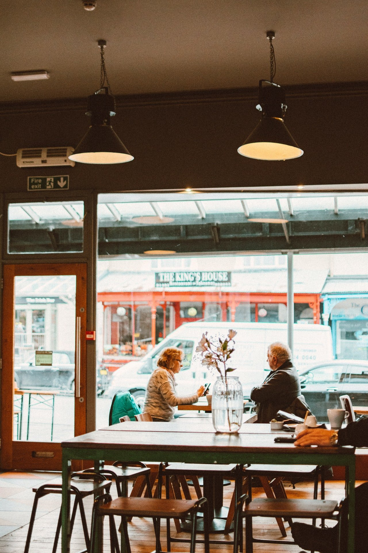 An elderly couple sitting by the window of a restaurant   Source: Pexels