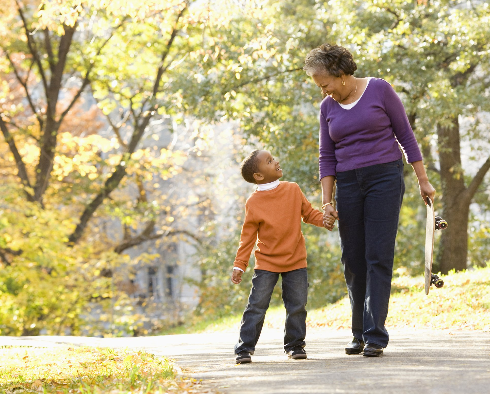Grandmother and granson walking in park smiling | Photo: Getty Images