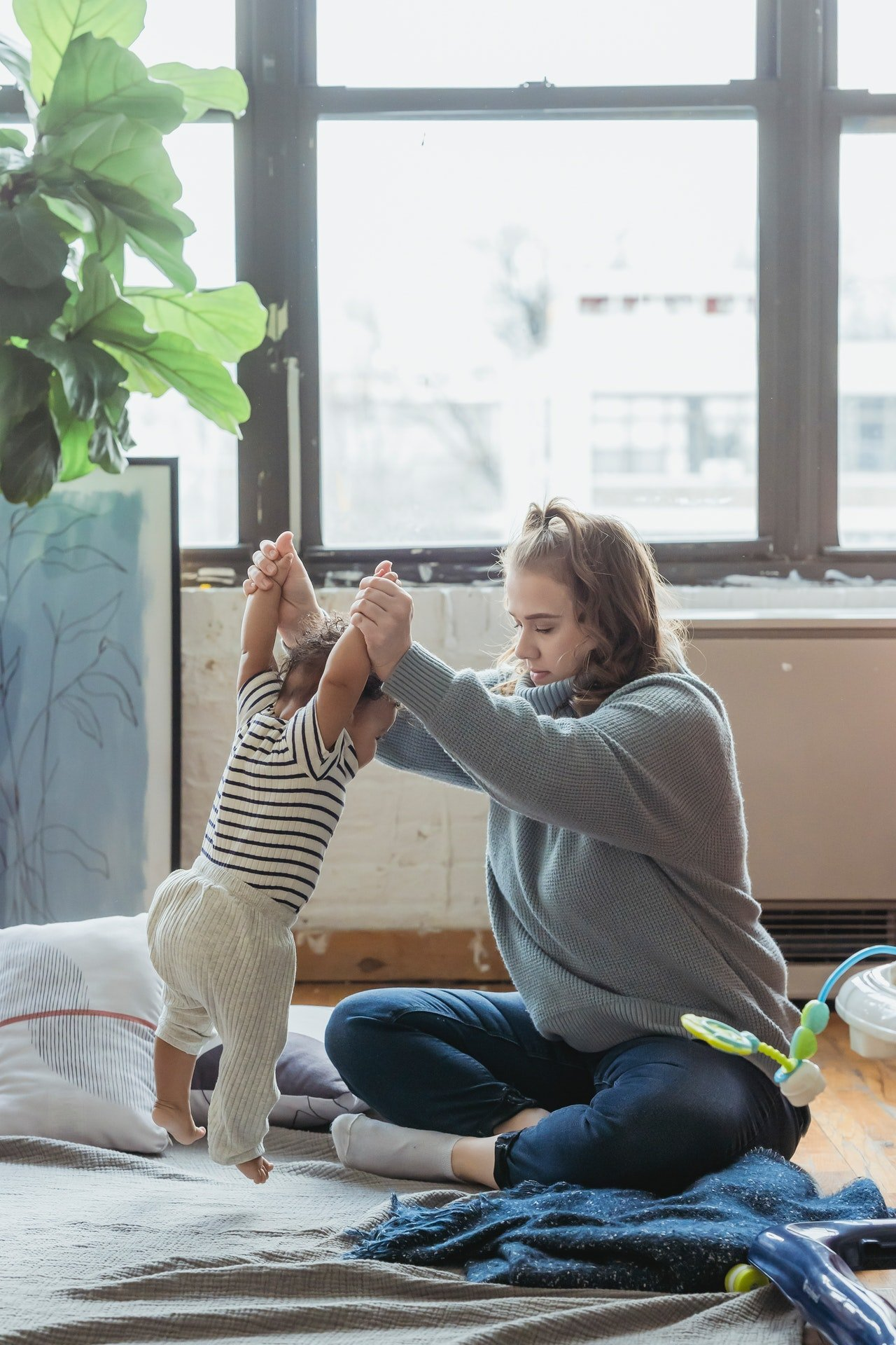 Woman playing with her baby on the floor | Source: Pexels