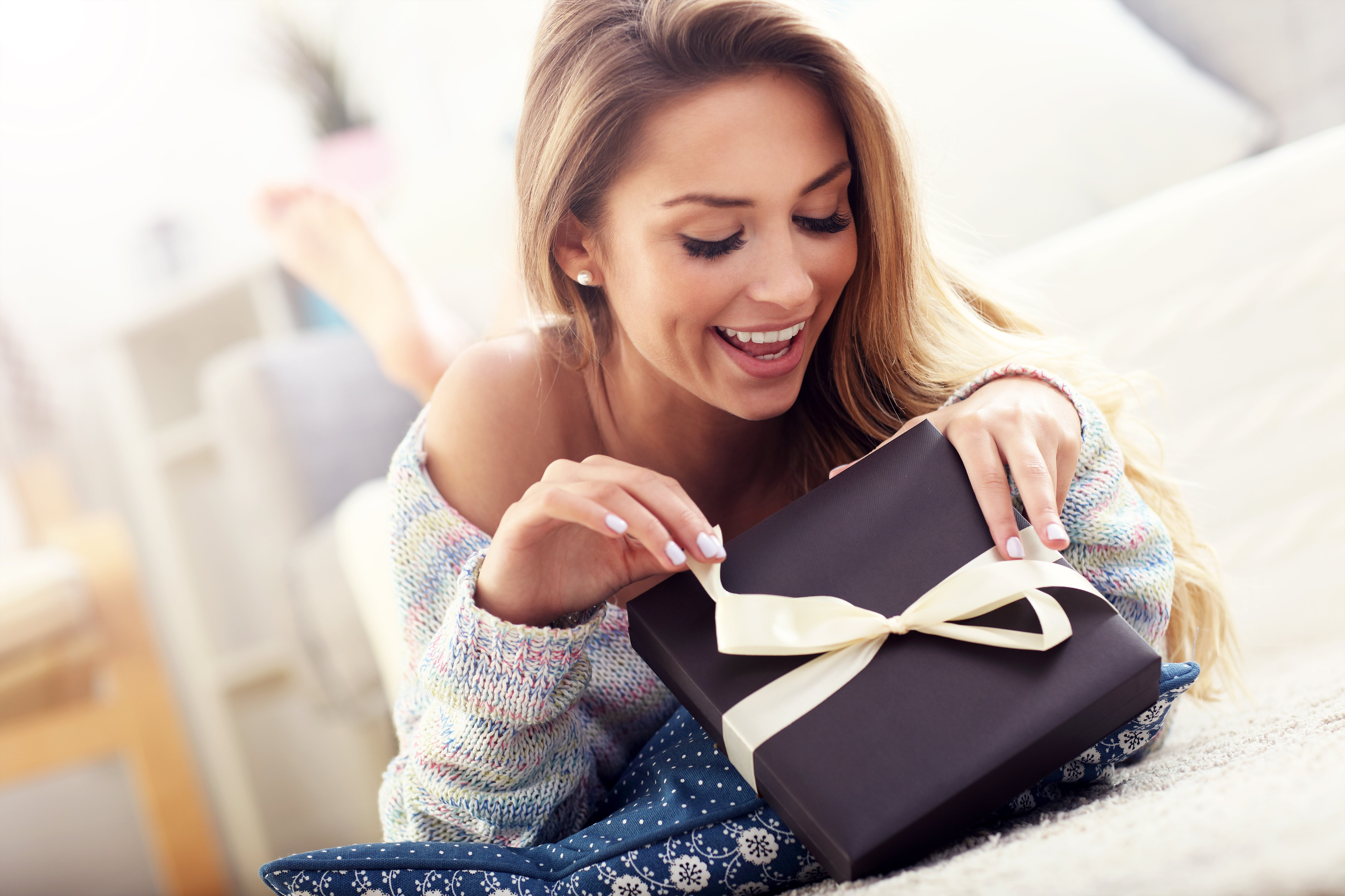 Woman excitedly opening a wrapped gift. | Source: Shutterstock